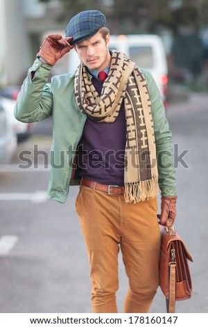 fashion man holding his hat as a greeting , outdoor picture