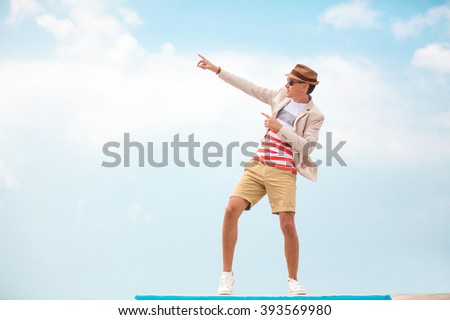 fashion man in hat and glasses pointing on copy space - stock photo