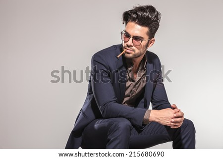 Fashion man in leather jacket looking down, sitting and holding his hands, studio shot - stock photo