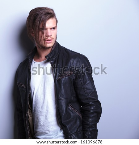 fashion man in leather jacket looks away from the camera while standing against a gray wall - stock photo