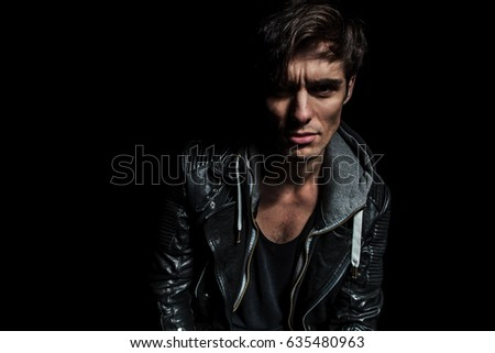 fashion man in leather jacket looks to the camera on dark background