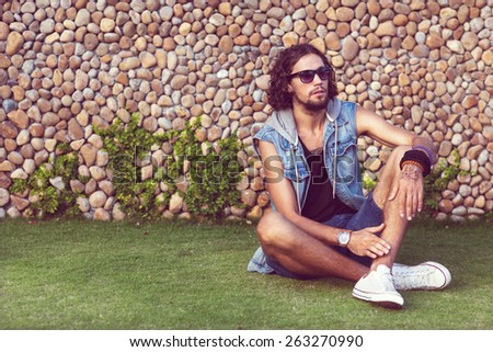 fashion man in sunglasses and jeans clothes sits on grass near palms and smiling Vogue - stock photo