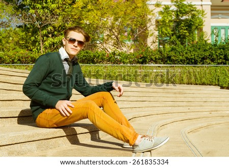 Fashion man in sunglasses, jacket and jeans is sitting on stairs  - stock photo