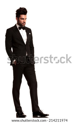 fashion man in tuxedo looking to his side, full body picture on white background - stock photo