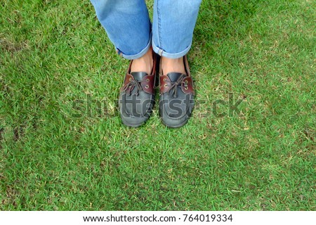 Fashion Man is Legs in Blue Jeans and Wear Vintage Shoes on Green Grass Background Great for Any Use.