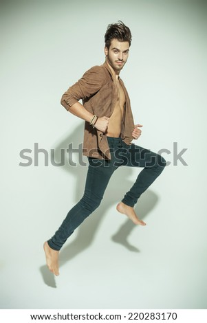 Fashion man jumping against grey background, pulling his jacket while looking at you - stock photo