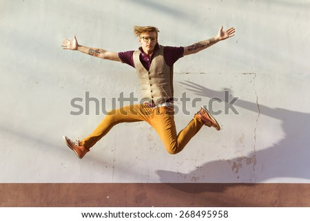 Fashion man jumps on background of white wall. City concept - stock photo