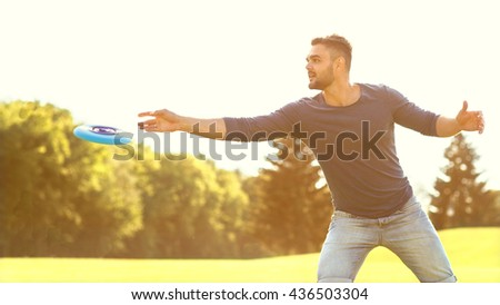 fashion man playing frisbee in the park - stock photo