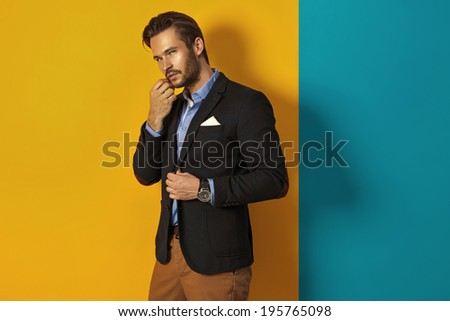 Fashion man posing in studio - stock photo