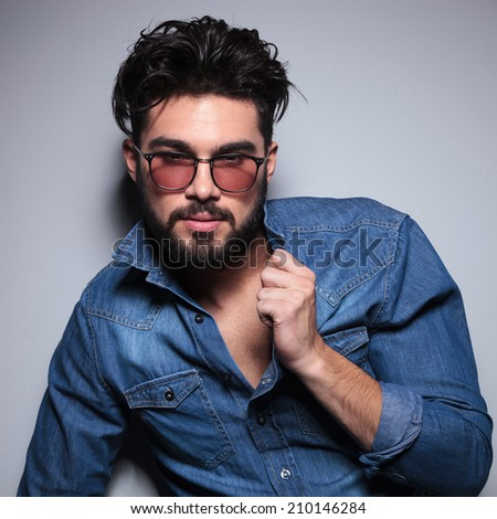 fashion man pulls his collar and looks to the camera in studio - stock photo