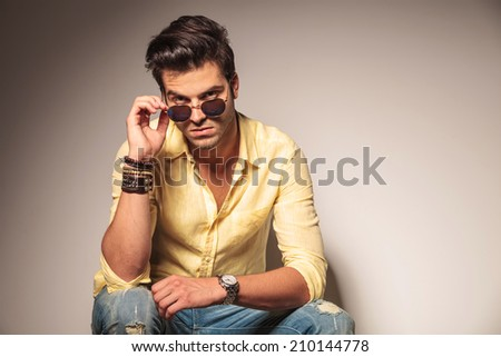 fashion man taking off his sunglasses and looks to the camera while seated on chair - stock photo
