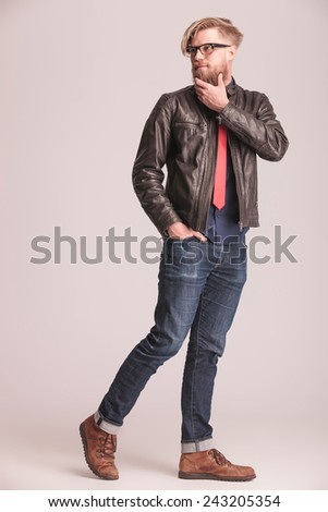 Fashion man walking on studio background holding one hand in his pocket while fixing his beard and looking away from the camera. - stock photo
