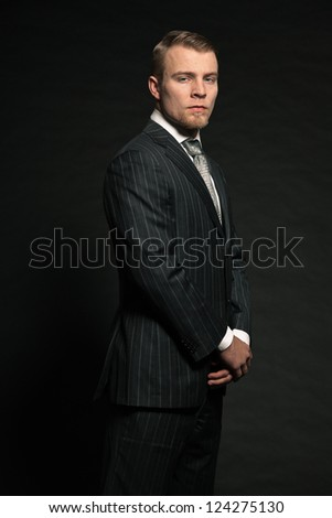 Fashion man wearing grey suit. Studio shot against black.