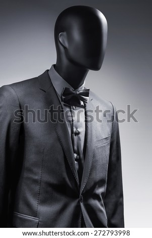 Fashion mannequin in elegant black suit over dark grey background. Black White photo - stock photo