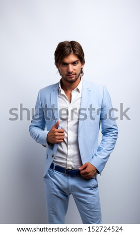 Fashion men, male model wear blue suit, young man over gray background - stock photo