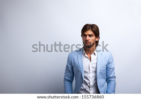 Fashion men, male model wear blue suit, young man with copy space over gray background - stock photo