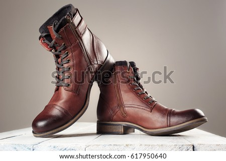 fashion men's boots.brown shoes still life on wooden table. man stuff