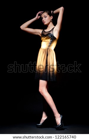 Fashion.Model.Background.Space. Slim model posing in a studio in the dark. A girl in a luminous golden dress - stock photo
