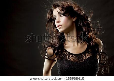 fashion model brunette wearing black outfit on black background - stock photo