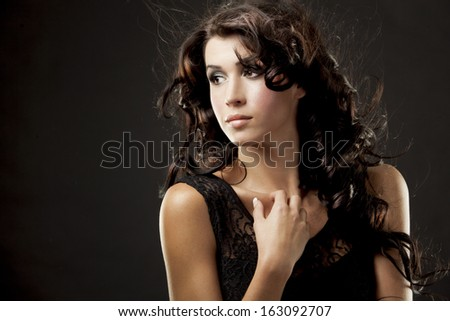 fashion model brunette wearing black outfit on black background
