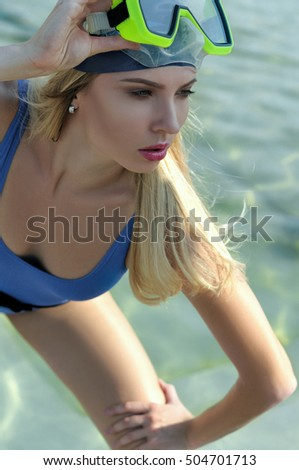 Fashion model demonstrates leotard and diving mask on the water background. The concept of active life and water sports.