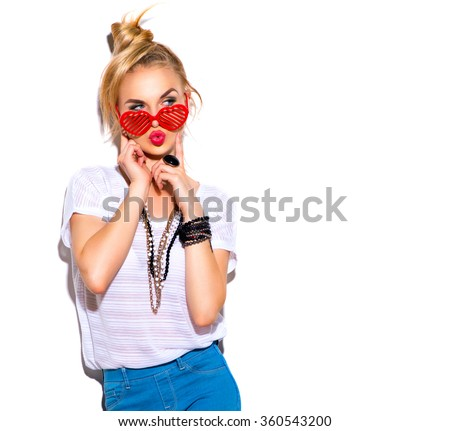 Fashion Model girl isolated over white background. Beauty stylish blonde woman posing in fashionable clothes and heart shaped sunglasses. Casual style with beauty accessories. High fashion urban style - stock photo