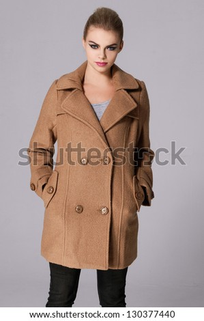 Fashion model in a coat posing at the studio. Isolated over gray - stock photo