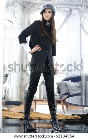 fashion model in autumn/winter clothes in hat posing in the studio - stock photo