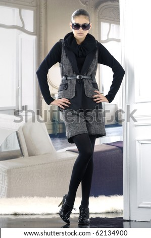 fashion model in autumn/winter clothes wearing sunglasses posing in the studio - stock photo