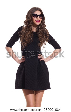 Fashion Model in Black Mini Dress. Beautiful young woman in sunglasses and black mini dress posing with hands on hip. Three quarter length studio shot isolated on white. - stock photo