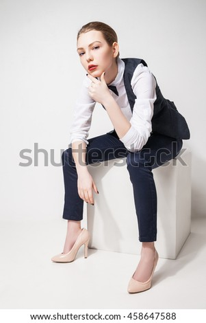 fashion model in black trousers, top, bow tie and vest sitting on cube over white