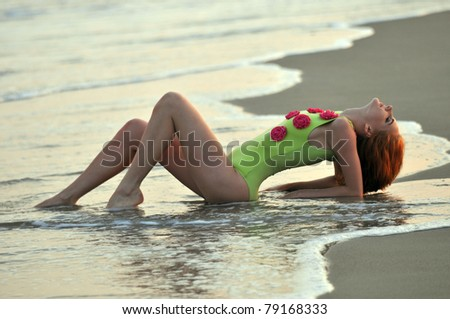 Fashion model in custom design lime color swimwear with flowers lying down on the sunset beach in Reese Park, NY - stock photo
