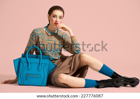 Fashion model in design clothes and blue bag posed on light color background