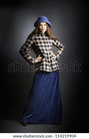 Fashion model in elegant autumn dress. Young woman in blue long skirt hat and checkered jacket