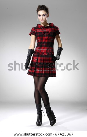 fashion model in fashion dress posing in light background in the studio - stock photo