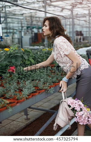 Fashion model in greenhouse with flowers. Stylish look. Beautiful dress. Outdoors.