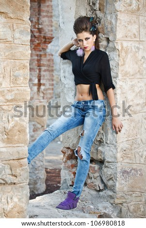 Fashion model in jeans against old stone wall, outdoor shot