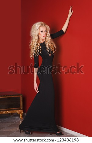 Fashion model in long black dress posing in glamorous red interior