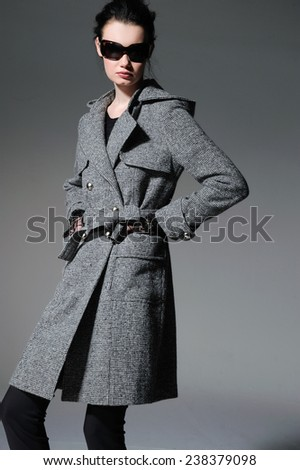 Fashion model in modern coat with sunglasses posing on gray background