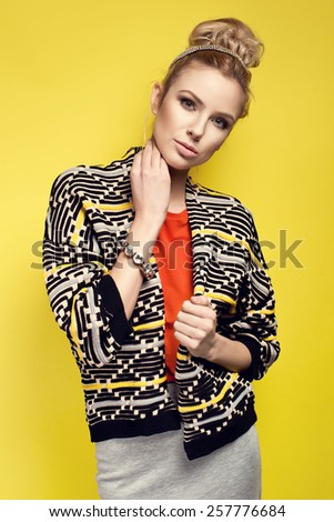 Fashion model in nice clothes posing in the studio on yellow background - stock photo