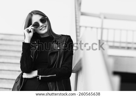 fashion model in sunglasses and black leather jacket posing outdoor. Black and white image - stock photo