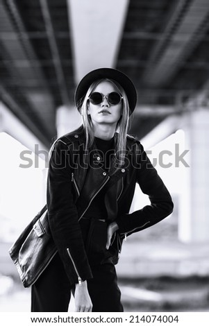 fashion model in sunglasses, hat and black leather jacket posing outdoor. Black and white image  - stock photo