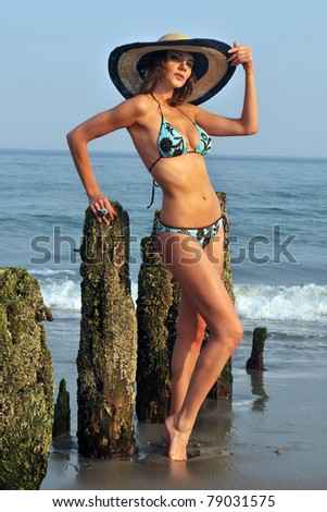 Fashion model in the hat and blue bikini bathing suit - stock photo