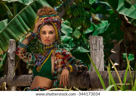 Fashion model in turban posing outdoors with jungle background - stock photo