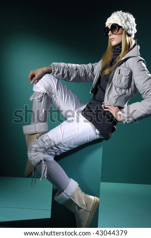 Fashion model in winter dress on blue light studio - stock photo