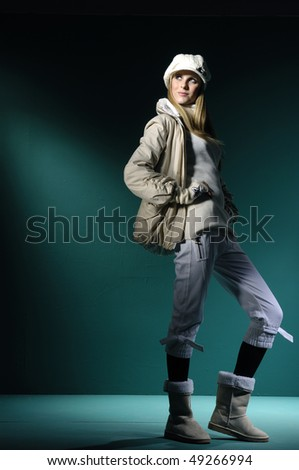Fashion model in winter dress on blue light studio