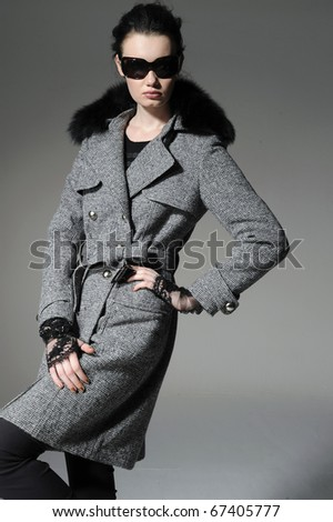 fashion model in winter fur coat clothes posing in the studio