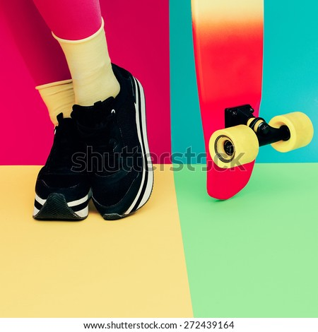 Fashion Model legs with Skateboard on bright exclusive background - stock photo