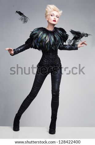 fashion model like bird posing with birds made of smoke on a reflective platform - stock photo