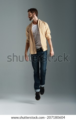Fashion model man with hipster beard jumping and having fun in studio - stock photo